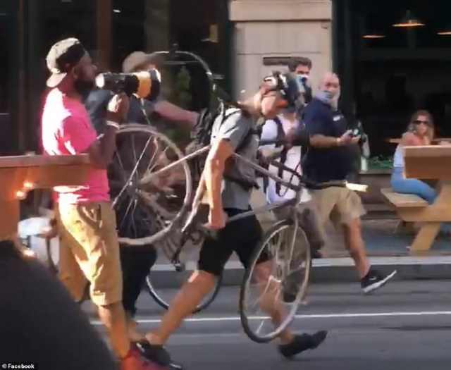One demonstrator and a cyclist get into a brief slapping match as others watch the exchange from restaurants and businesses (pictured)