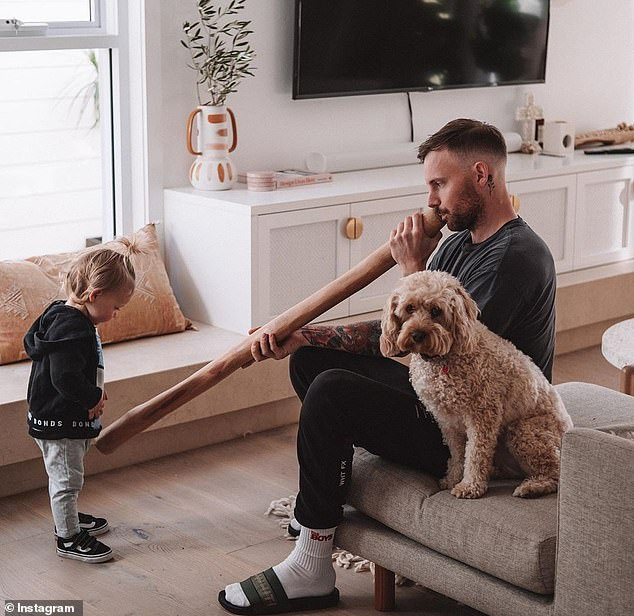 The fitness blogger's partner Kurt Tilse uploaded an image (pictured) of himself playing the Aboriginal instrument for his one-year-old son Fox to Instagram on Sunday