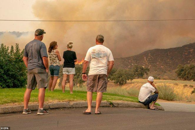 Residents watch as the El Dorado Fire burns a hillside near Yucaipa in the San Bernardino National Forest on Monday