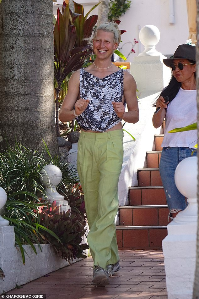Quirky:Meanwhile, Christian, who recently dyed his hair and brows platinum blond, opted for a backless sequin top, pastel green trousers and chunky grey trainers