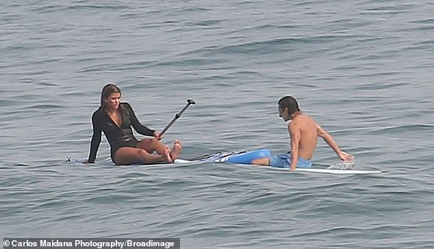 Chatty: She was joined by her good pal Moisés Arias, 26, who swam up beside her on his surf board