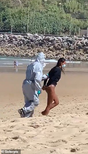 The woman was then seen in a mask being led away by Hazmat-wearing officials (pictured)
