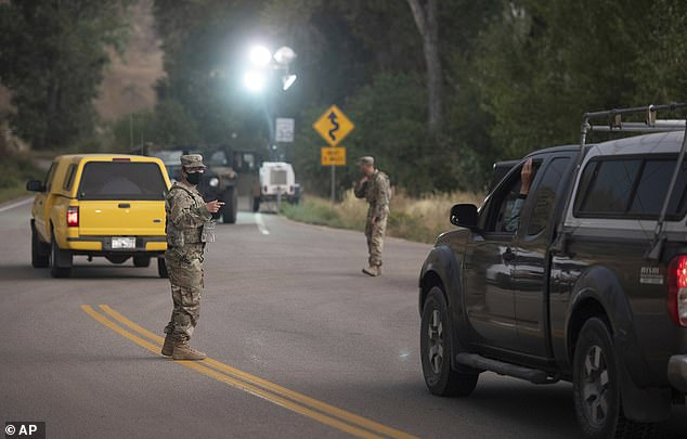 A member of the Colorado National Guard directs motorists at a roadblock after forced evacutaions