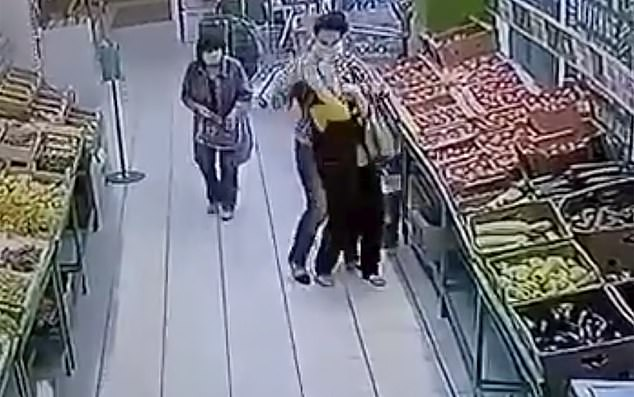 The woman, wearing a medical face mask, approaches the victim at the fruit aisle from behind as another shopper looks on helplessly before the attack