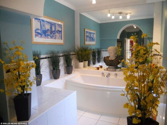 Come on in: The master bathroom features a tiled floor and a generously sized tub, surrounded by potted plants