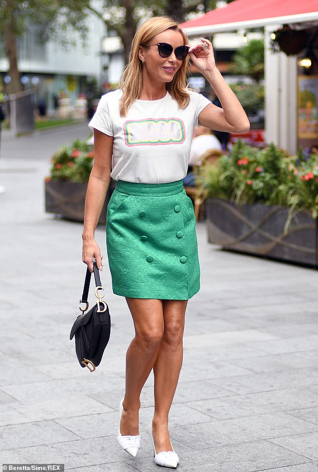 Dressed up well: Amanda completed her look with a black handbag and cat-eye sunglasses