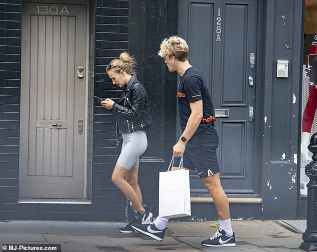 Multi-tasking: They put on an equally sporty display - Tiff in a black top and grey skinny gym shorts, a black leather jacket, shoulder purse and trainers added to the look