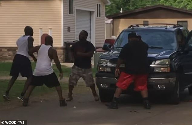 Weaver (far left) is seen in the video throwing punches at the ex-boyfriend (wearing the dark shirt and camo shorts)
