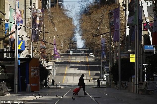 A person is seen walking across a quiet Bourke Street on September 6