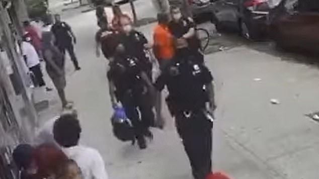 New York Police Department officers are seen above hauling the suspect away in handcuffs