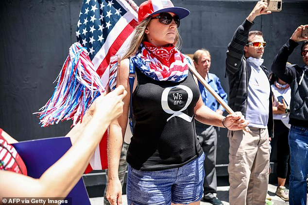 The boogaloo movement is a far-right anti-government extremist movement and has oftentimes been described as a militia. QAnon (demonstrator pictured) is a conspiracy theory that has undertones of antisemitism and xenophobia