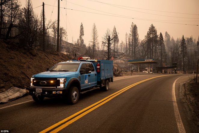 A Pacific Gas and Electric Company truck drives past a destroyed petrol station on State Route 168 in northern California