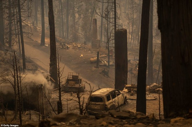 Charred machinery, cars and buildings smolder in the Meadow Lakes area of California following the Creek Fire