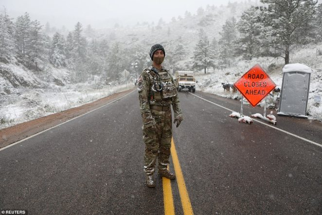 Colorado National Guard members monitor a roadblock leading to the Cameron Peak wildfire as snow falls on Tuesday