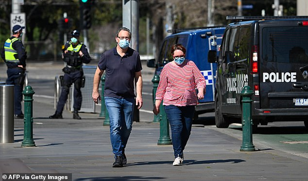 A face mask wearing couple takes a walk as police look on in Melbourne on September 6, 2020