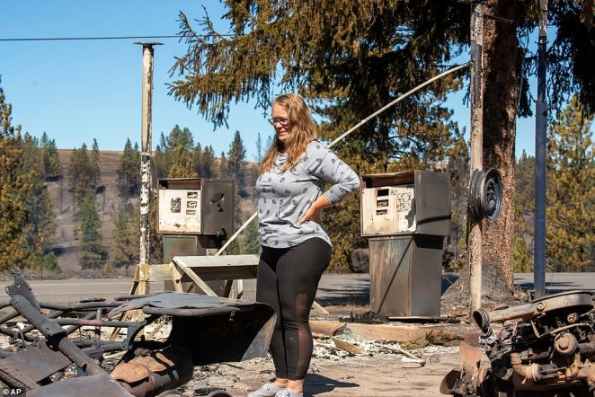 "Hollie Jordan surveys her father's service station that was destroyed by wildfire in Malden, Washington, on Tuesday. ""This was filled with work and life and memories and it's all gone,"" said Jordan"