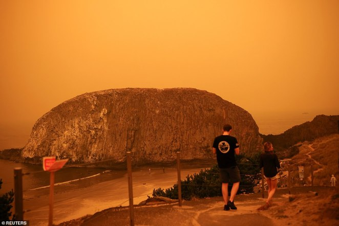 People walk by the Pacific Ocean coast as smoke from wildfires covers an area near Seal Rock, Oregon on Tuesday