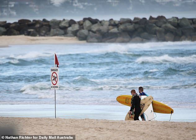 Two surfers are seen walking near a 'danger' sign on Wednesday morning as beaches are shut from Burleigh to Snapper Rocks