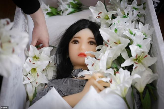 Flowers are placed next to a sex doll named Ran laying inside a coffin during her funeral service at the photography studio