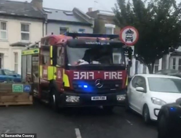 The video shows the blue-lit emergency vehicle appearing to be wedged between a wooden planter and a parked white vehicle in Ferndale, south London