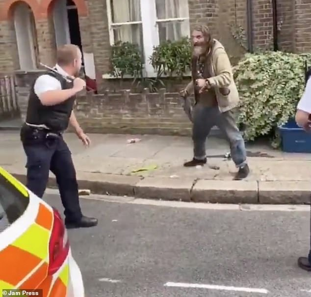 Moments later, the male police officer stands with a baton in his hands and tells the man to get down
