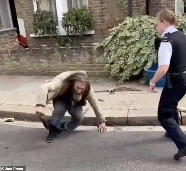 The man jumps back to his feet after being hit by the taser gun as the two officers stand back