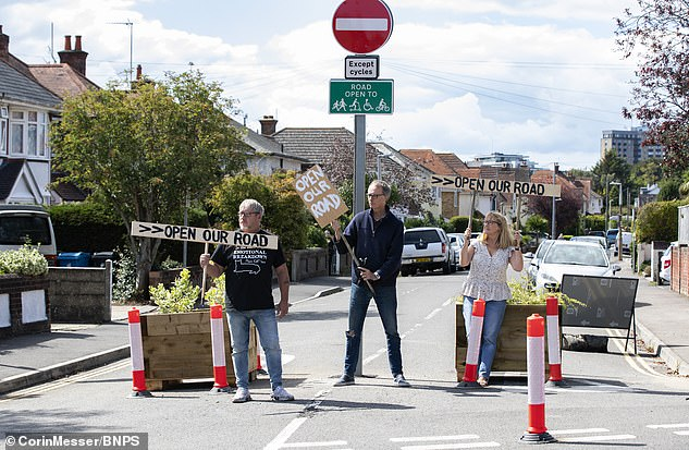Angry residents on Churchfield Road, in Poole, planted signs in protest against their street being closed off, placing them in timber containers