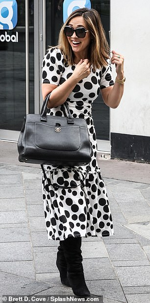 Arm candy:The TV and radio presenter put her love for Chanel on full display with a classic designer leather tote bag with the gold 'CC' logo emblazoned on the front