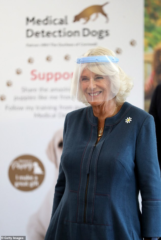 The Duchess of Cornwall grinned as she went inside the training center to meet employees