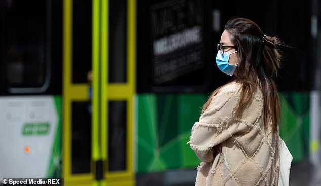 A woman wearing a face mask is seen waiting for a tram in Melbourne on Wednesday.