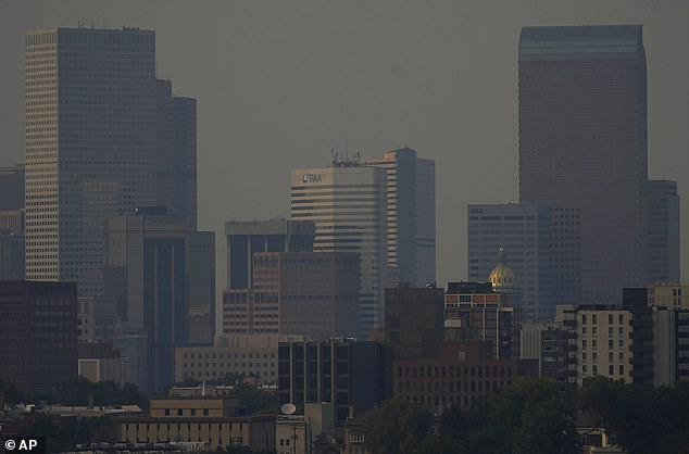 Smoke from the Cameron Peak wildfire is seen over Denver on Sunday morning. Snow would be falling in the city less than 24 hours later