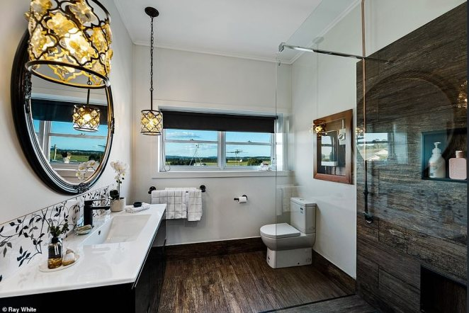 Agricultural-inspired features are cleverly contrasted with modern fixtures like stainless steel tapware and ornate hanging lamps in the bathroom