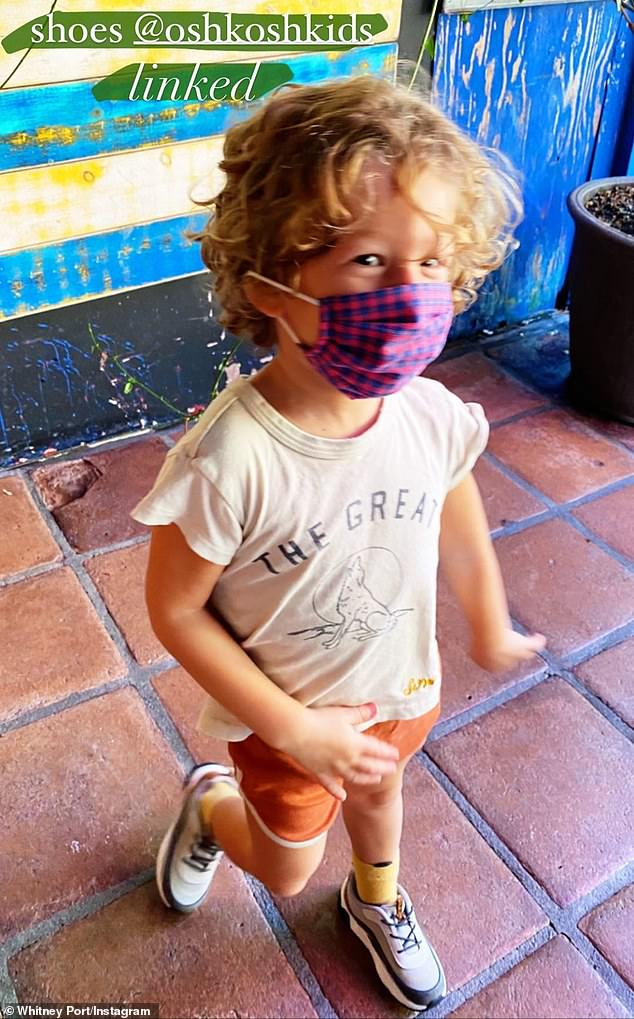 Cute: Joining Whitney on her errand run was her three-year-old son Sonny, who wore a T-shirt with a wolf on the front, orange shorts and a red and blue gingham mask