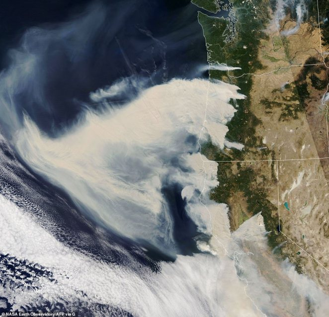 NASA's Aqua satellite captured this natural color image of thick smoke plumes streaming west from a long line of intense fires in Washington state, Oregon and California