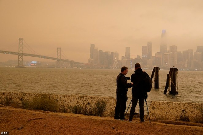 People from San Francisco to Seattle woke Wednesday to hazy clouds of smoke lingering in the air, darkening the sky to an eerie orange glow that kept street lights illuminated into midday, all thanks to dozens of wildfires throughout the West