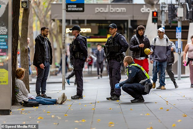 Police are pictured speaking to a man outside Melbourne Town Hall on May 28 while enforcing COVID-19 restrictions. (There is no suggestion anyone pictured has done anything wrong)