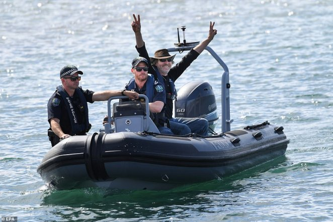 Two deadpan police officers drive Mr Robinson to shore as the elated fisherman threw threw his hands in the air