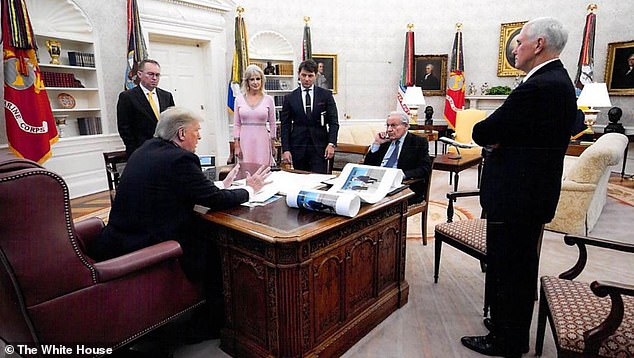 In this White House photo from December 2019 provided by Bob Woodward, President Donald Trump is seen speaking to Woodward in the Oval Office, surrounded by some aides and advisers, as well as Vice President Mike Pence, then acting Chief of Staff Mick Mulvaney, then-White House counselor Kellyanne Conway and then-deputy press secretary Hogan Gidley. On Trump's desk is a large picture of Trump and North Korean leader Kim Jong Un.