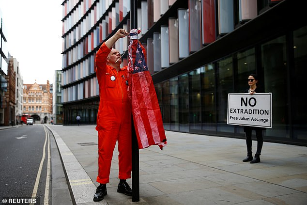 A supporter of Assange ties a US flag to a lamp post outside the Old Bailey.A US grand jury indicted Assange on 18 charges - 17 of which fall under the Espionage Act