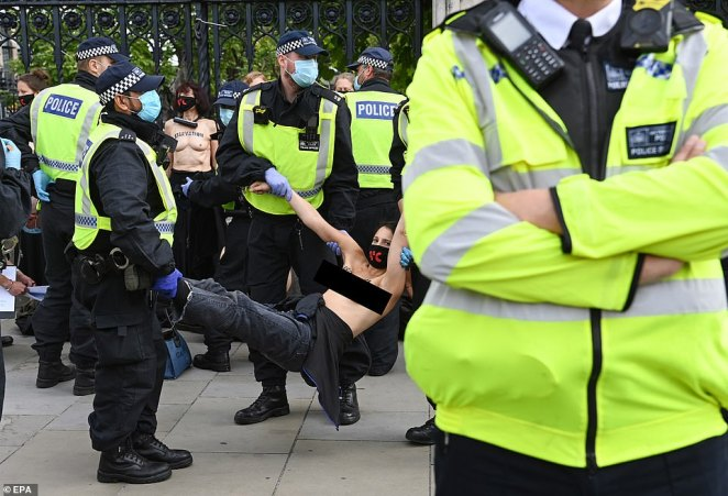 Topless protesters are removed by police after they locked themselves to the railings of Parliament during a climate protest