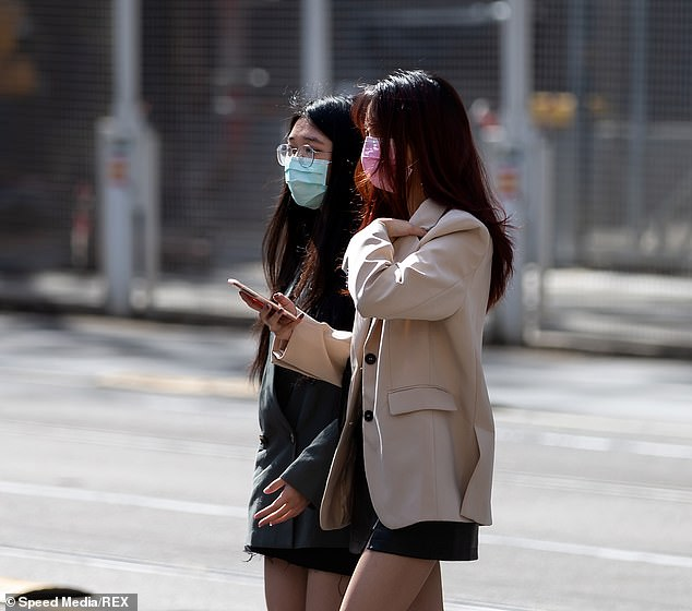 Two young woman walk across an intersection in the Melbourne CBD on Thursday. Sweden's unenforced mask recommendations are a far cry from the Victorian capital's Stage Four restrictions