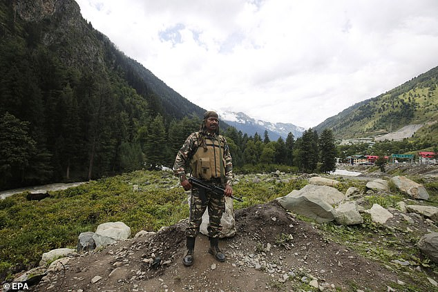 An Indian security personnel stands guard after shots were fired for the first time in 45 years this week