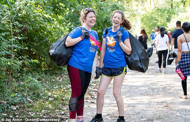 'In the early days of the International Coastal Cleanup, volunteers were finding glass bottles, metal cans, paper bags, and other items that have increasingly been replaced by plastic alternatives,' said Ocean Conservancy director Allison Schutes. Pictured, volunteers carry the waste they collected during the 2019 International Coastal Cleanup effort in Washington