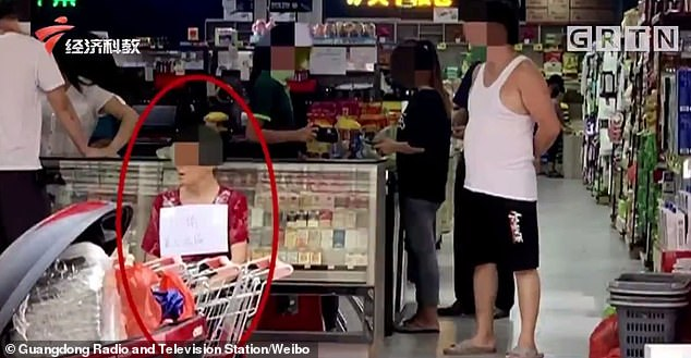 A picture shows the woman sitting outside a supermarket in China with a sign around her neck