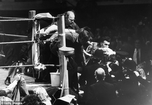 American boxer Marvin Hagler leaving the ring with a police escort after his fight with Minter