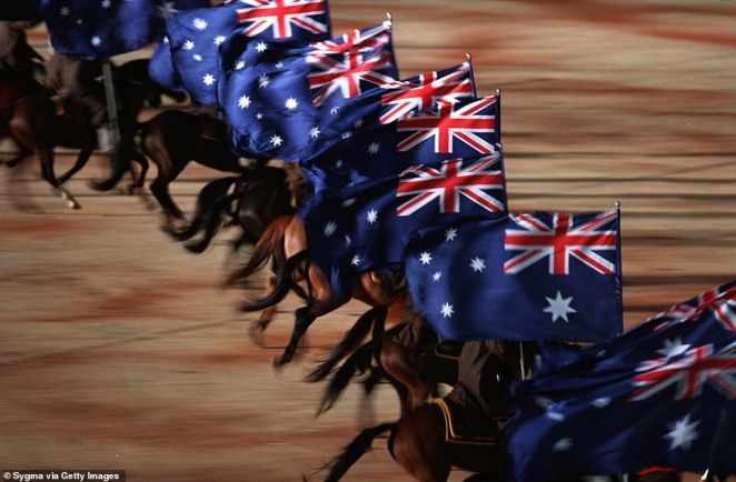 Stockman riding horses and carrying the Australian flag (pictured) rode into the stadium as part of the opening ceremony