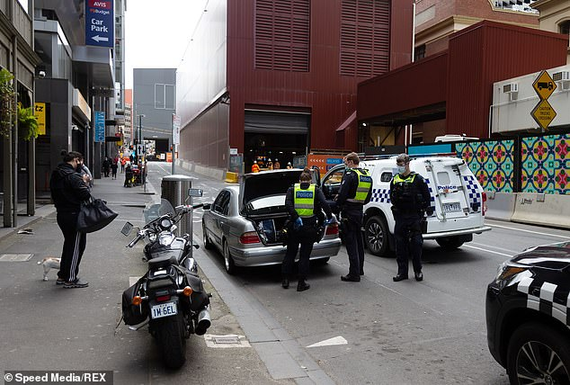 Melbourne's five million residents on August 2 were placed into a strict lockdown banning them from travelling more than 5km from home and being outside after 8am. Pictured are police in Melbourne on September 9, 2020 searching the boot of a Mercedes-Benz E-Class