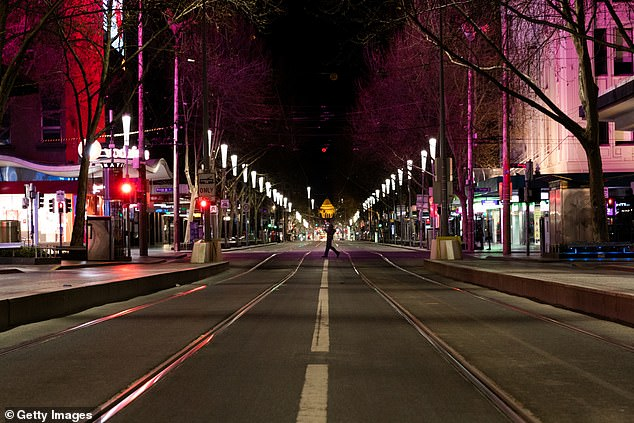 The expert behind Melbourne's economically destructive Stage Four lockdowns has admitted the measures won't prevent a third wave of coronavirus. Pictured is a deserted intersection at Swanston and Bourke streets on September 10, 2020