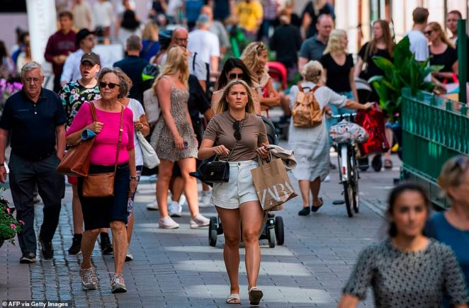 People walk on a street in Stockholm where masks are not required and shops and restaurants have remained open throughout the pandemic, with Swedes trusted to take necessary hygiene measures themselves