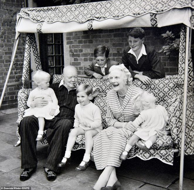 Black and white photograph show Winston Churchill with his grandchildren and wife at his family home in Kent